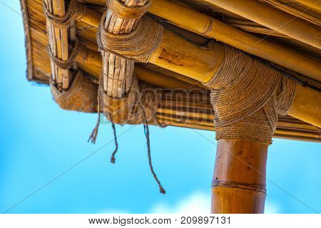 The bamboo canopy is tied with a rope to the support on the blue sunny sky. Life and interior items of the Gili Trawangan island, Indonesia.