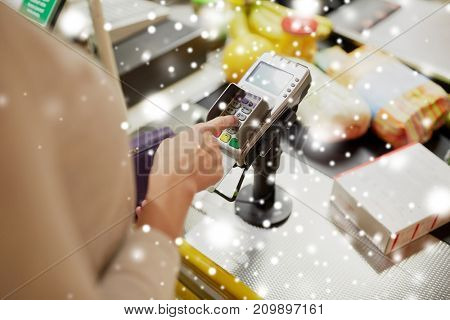 shopping, sale, consumerism and people concept - woman buying food at grocery store or supermarket cash register and entering pin code over snow