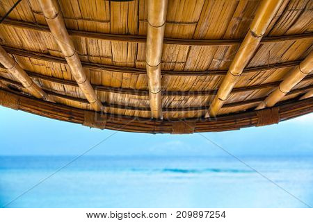 A bamboo roof against the background of the horizon the border of the sea and sky. Life and interior items of the Gili Trawangan island, Indonesia.