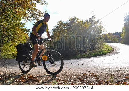 Traveler rides a bicycle along a winding mountain road. Cyclist on the road on sunny autumn day