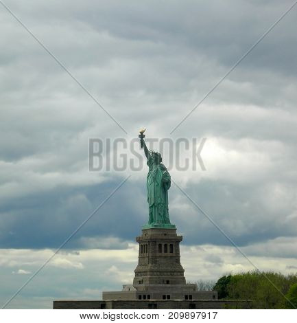 Lady Liberty seen from the front with a grey and cloudy sky as background in Manhattan New York City