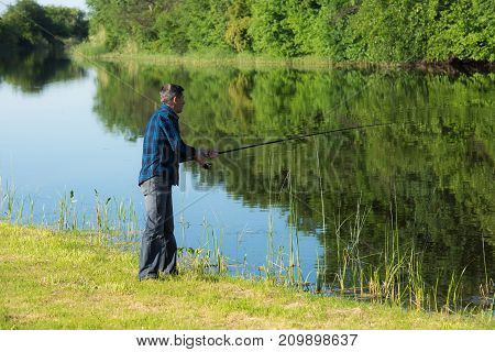 Retired man is fishing whith the rod. He is standing at the bank near calm small and narrow river. Bank is covered by short green grass. The blue sky is reflected in river. Unfocused green forest at the background.