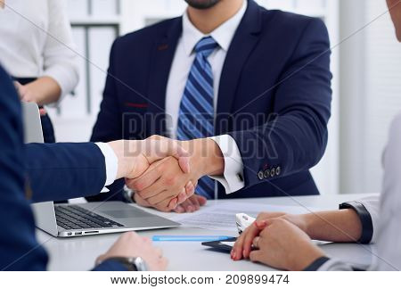 Business handshake at meeting or negotiation in the office, close-up. Partners are satisfied because signing contract or financial papers.