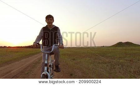 Boy teenager riding bicycle. Boy teenager riding bicycle goes to nature along path steadicam shot motion video