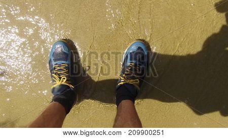 Men legs in sneakers. Man is standing on seashore sand waves wet sneakers traveling rest