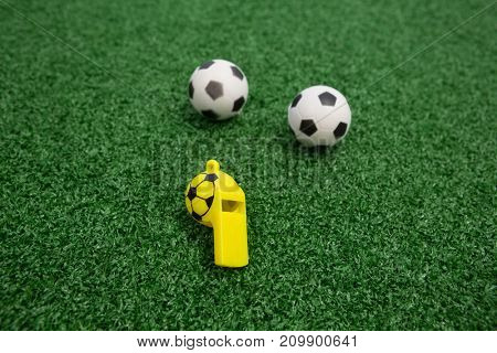 Close-up of whistle and footballs on artificial grass