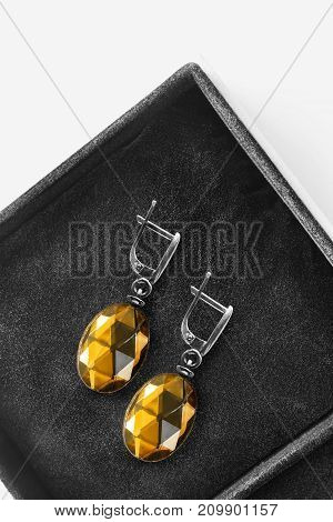 Amber faceted earrings in black jewel box closeup