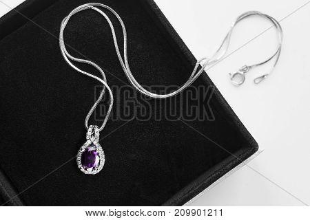Purple amethyst pendant with diamonds in black jewel box