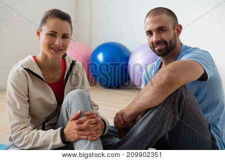 Portrait of female student and instructor relaxing in yoga studio