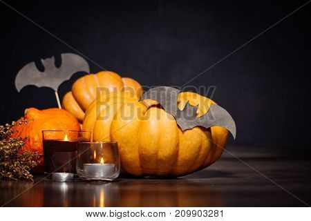 composition for decorating a house for halloween, lie yellow and orange pumpkins, burning scented candles, yellow leaves