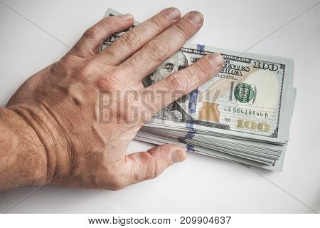 Male Hand Covers A Bundle Of Us Dollars