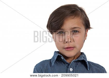 Portrait of cute boy standing against white background