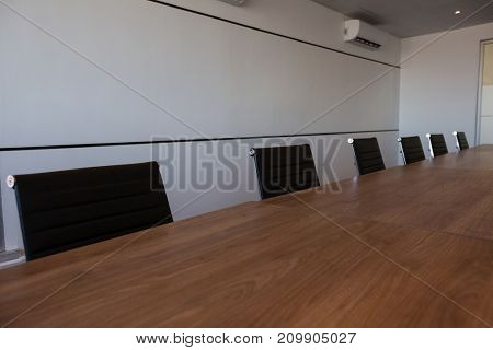 Empty office chairs at conference table in modern meeting room