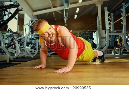 A fat man does push-ups in the gym.