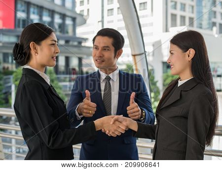 business man show thumb up and two business woman shaking hands and smile for demonstrating their agreement to sign agreement or contract between their firms companies enterprises. success concept