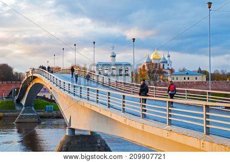 VELIKY NOVGOROD RUSSIA -OCTOBER 19 2017.Saint Sophia Cathedral with belfry and people walking on the footbridge in Veliky Novgorod Russia