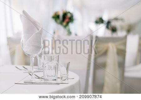 Table set for an event party or wedding reception on white tablecloth. White soft background with tables and flowers
