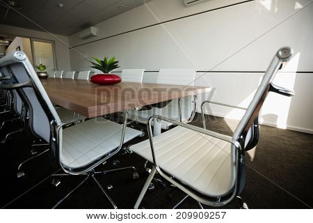 Empty chairs by conference table at modern office