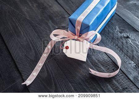 Cute present wrapped in blue paper and tied with pink ribbon and bow with a blank tag attached to it on an old wooden table.
