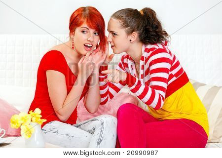 Girl whispering gossips in ear of her interested girlfriend and pointing finger in corner
