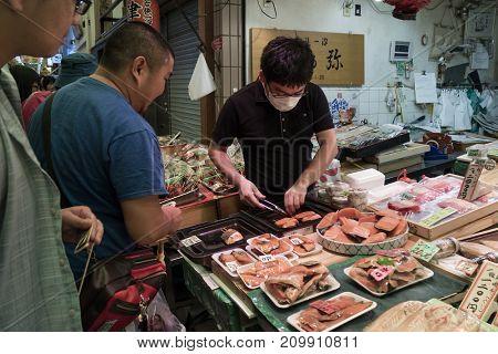 Kyoto, Japan -  May 22, 2017: Preparing and selling fresh raw fish at the Nishiki market, Kyoto's Kitchen in kyoto