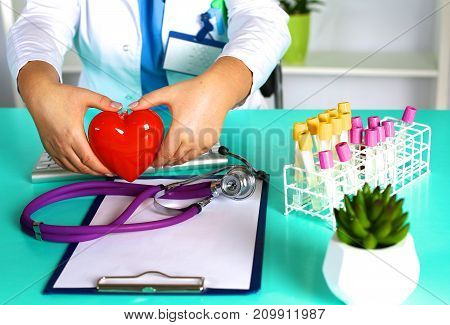Female doctor with stethoscope holding heart. Doctor and patient sitting in the background.