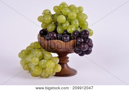 clusters of grapes of different varieties in a wooden bowl.