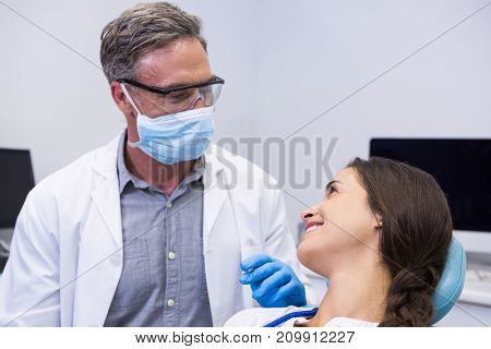 Dentist talking with woman at medical clinic