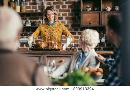 young woman with thanksgiving turkey for holiday dinner with family