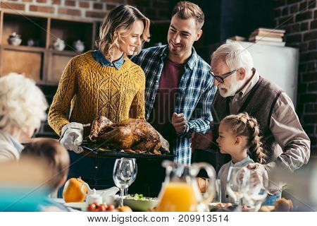 excited beautiful family looking at thanksgiving turkey