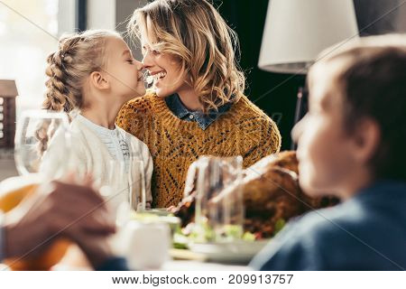 happy mother and daughter cuddling at thanksgiving holiday table