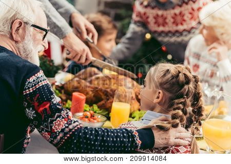 happy grandfather and little granddaughter talking at christmas table