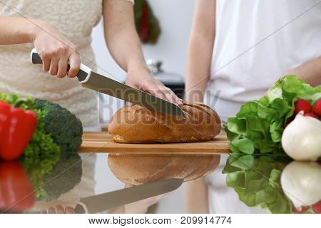 Close-up of human hands slicing bread in a kitchen. Friends having fun while cooking in the kitchen. Chef cook represent culinary masterclass.