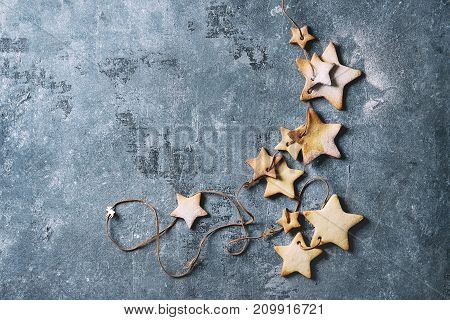 Homemade shortbread star shape sugar cookies different size with sugar powder on thread over blue texture surface. Christmas treat background. Top view with space. Toned image