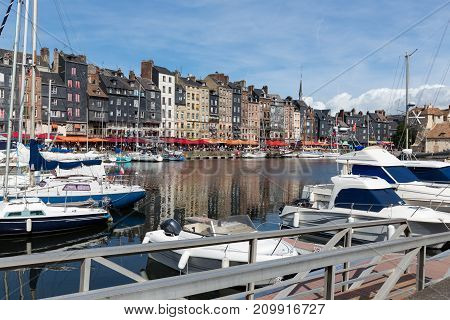 Saling boats in old medieval harbor of Honfleur, France. Tourists are relaxing at terraces along the harbor.