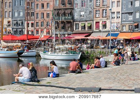 HONFLEUR, FRANCE - AUGUST 24, 2017: Harbor of historic city Honfleur with moord sailing ships. Many people are relaxing and sitting near the water