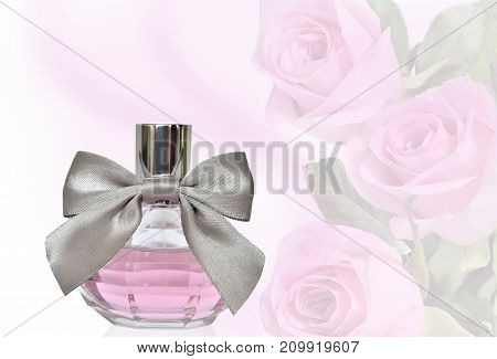 Women's perfume in beautiful round bottle with silver bow close up on a light floral background with pink roses