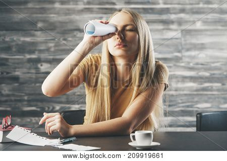 Bored young woman using rolled business report as binoculars while sitting at office desk with book coffee cup and other items. Boredom concept