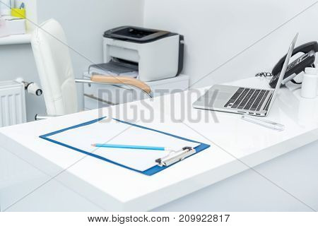 pediatrician workplace with laptop and clipboard at modern clinic
