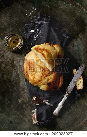 Homemade white wheat garlic bread on textile napkin with salt, olive oil and balsamic vinegar on old dark metal background. Top view with space