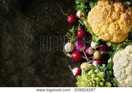 Variety of fresh raw organic colorful cauliflower, cabbage romanesco and radish with bundle of coriander over dark texture background. Top view with space. Healthy eating concept