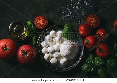 Ingredients for italian caprese salad. Mozzarella balls, buffalo in metal vintage plate, tomatoes, basil leaves, olive oil with vinegar over dark background. Top view. Rustic style. Toned image