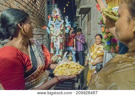KOLKATA INDIA - JUNE 17 2017 - Female Hindu devotees worshipping Goddess Kali at night during Kali Puja Hindu festival of Deepavali or Diwali. Celebtated all over India. Shot under mixed light.