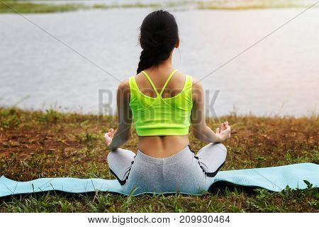 Young Asian Woman In Sportswear Meditating On Yoga Mat, Back View