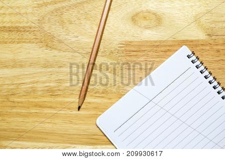 Notebook and pencil on wooden table top view shot