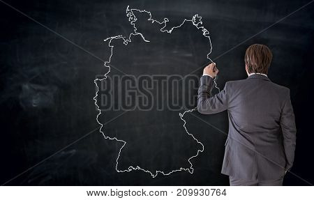 Businessman Painting Germany Map On Blackboard Concept