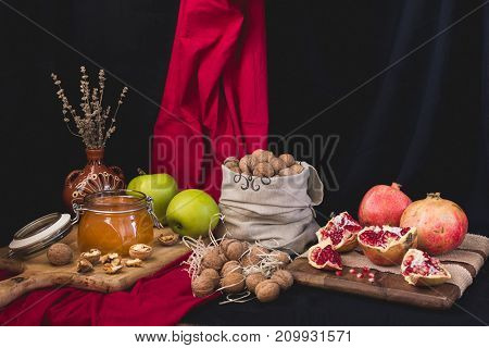 Autumn still life honey and apples on a wooden board, nuts in a bag, pomegranate on a wooden board wrapped with jute tape dry lavender in a clay vase on a red-black background
