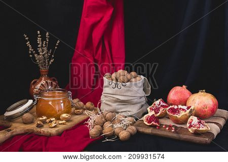 Autumn still life of a honey bank, nuts in a bag, pomegranate on a wooden board wrapped in jute tape dry lavender in a clay vase on a red-black background