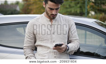 Handsome Young Man using mobile phone while leaning on his car