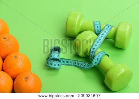 Oranges Near Dumbbells, Cyan Measuring Tape On Green Background